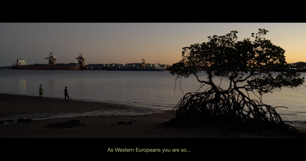 """Video Still, *INFRACTIONS*, 2019, 1:03:00, HD video, split screen with text, Dolby 5.1  Settlers fishing on Gooreng Gooreng country, Yallarm (Gladstone harbour). Voiceover, Professor Irene Watson:   *""""As Western Europeans you are so long in your disconnection from your own stories or laws of the land... At the critical time that we are now, globally, with climate change and the destruction of local ecosystems, when we think about what we have, to hold on to the future, to care for country, we have a Western European legal system that has no concept of those responsibilities.""""*"""