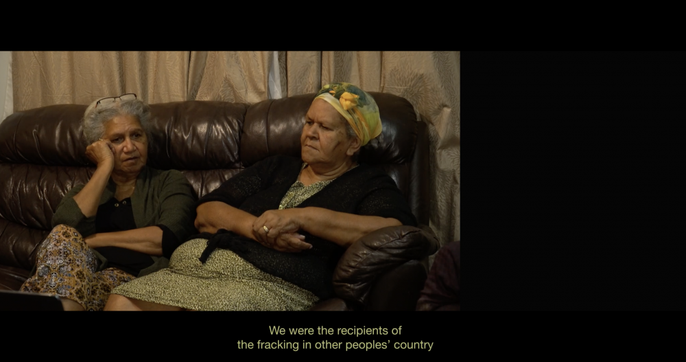 """Video Still, *INFRACTIONS*, 2019, 1:03:00, HD video, split screen with text, Dolby 5.1  Artist and educator Juliri Ingra and Neola Savage (Gooreng Gooreng) navigated Gladstone LNG Native Title negotiations under the threat of compulsory acquisition. Neola Savage:   *""""Every week I'd just cry, from when I turned at Rio Tinto and looked over and saw all those buildings. You know, if I had my chance again, I wouldn't sign…At least I would have peace of mind, you know, for the people that I represented. Because we got nothing out of it.""""*"""