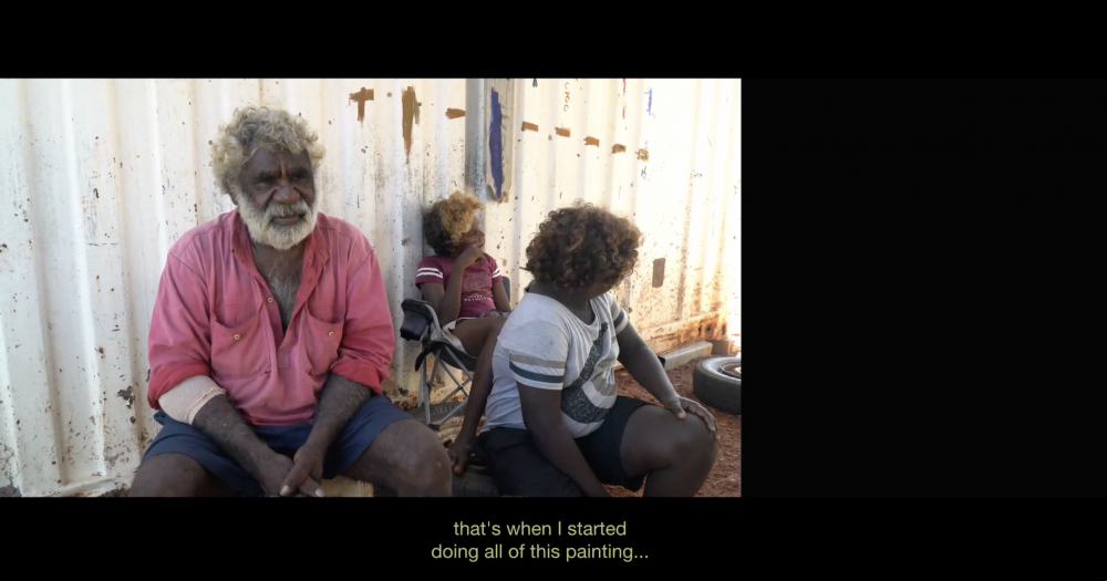 """Video Still, *INFRACTIONS*, 2019, 1:03:00, HD video, split screen with text, Dolby 5.1  Jack Green (Garawa, Gudanji) paints mine power in Gulf Country since the 2006 McArthur River Mine expansion cut sacred sites and leaked toxic waste into the river.  *What's in the back of their mind, they keep worrying about money, money, money, so they dig up the land, destroy the land, and that's also fracking doing the same thing. They can never tell us what damage can happen down the bottom… This land, it will give up somewhere on us, you know?""""*"""