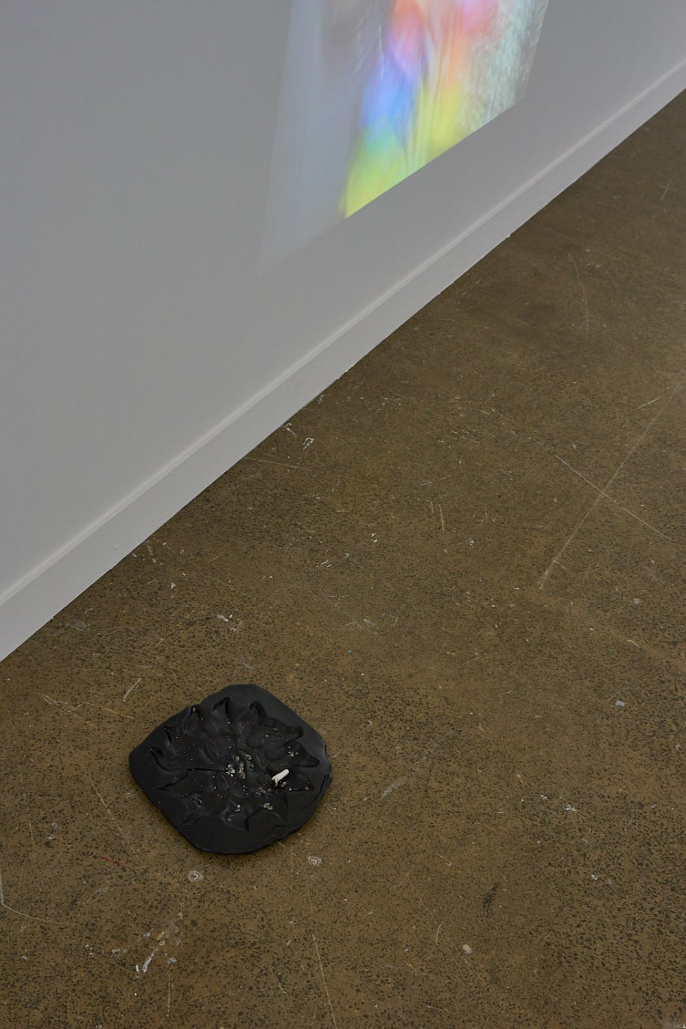 *Outsider Artifact* Sun sculpture from the entranceway to 'Basement Specialist Adult Store and Cruise Club' imprinted in non-firing natural clay, acrylic paint, cigarette butt, ash. Daniel John Corbett Sanders 2019  Image: Andreea Christache